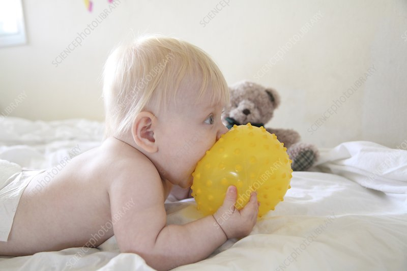 Baby eating a yellow ball