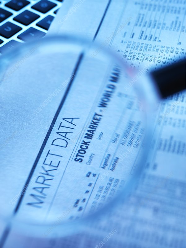 Stock market figures and magnifying glass