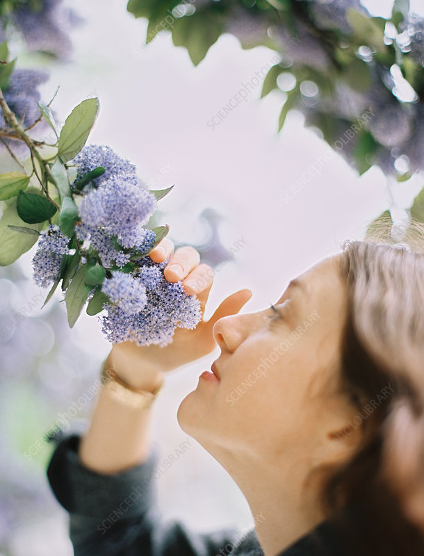 A woman inhaling scent of a blue flower
