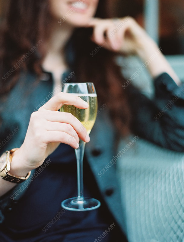 A woman holding a glass of white wine