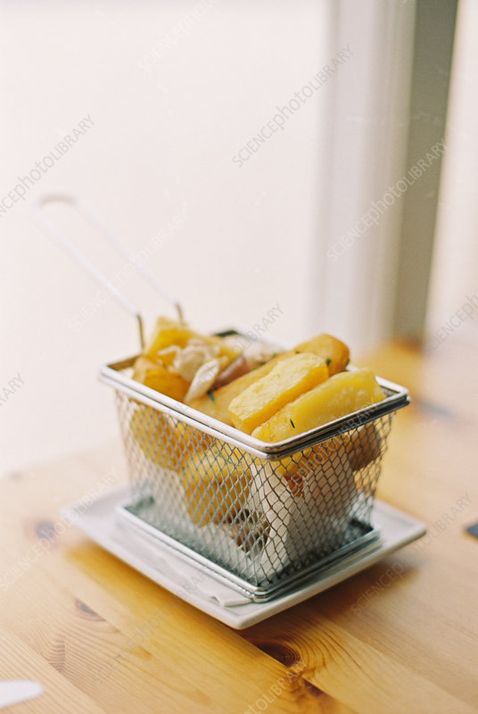 A small wire basket of fried potatoes