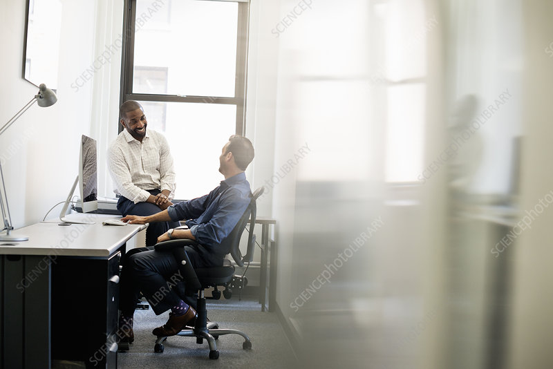 A man leaning back talking to a colleague