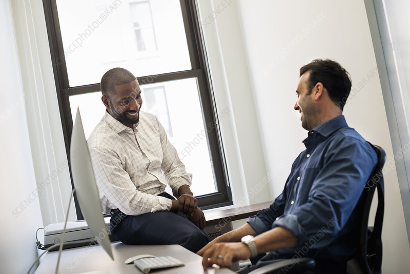 A man talking to a colleague in an office
