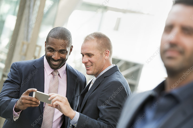 Two businessmen checking a phone