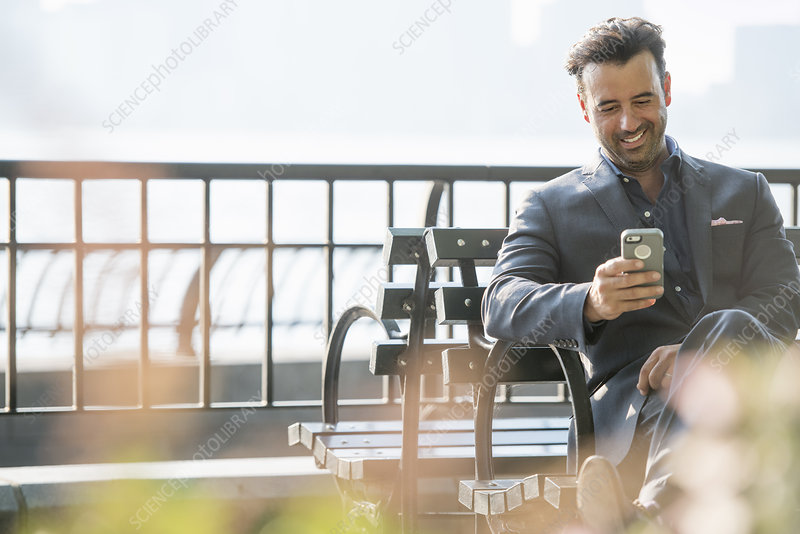 A businessman seated checking his phone