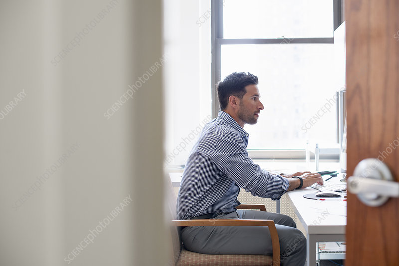 A man sitting at a desk using a computer
