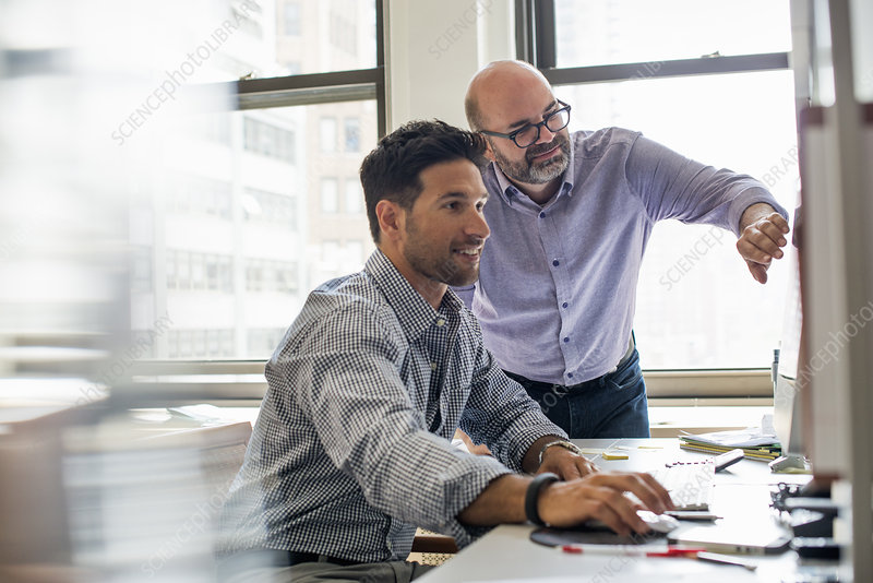 Two men in an office, using a computer
