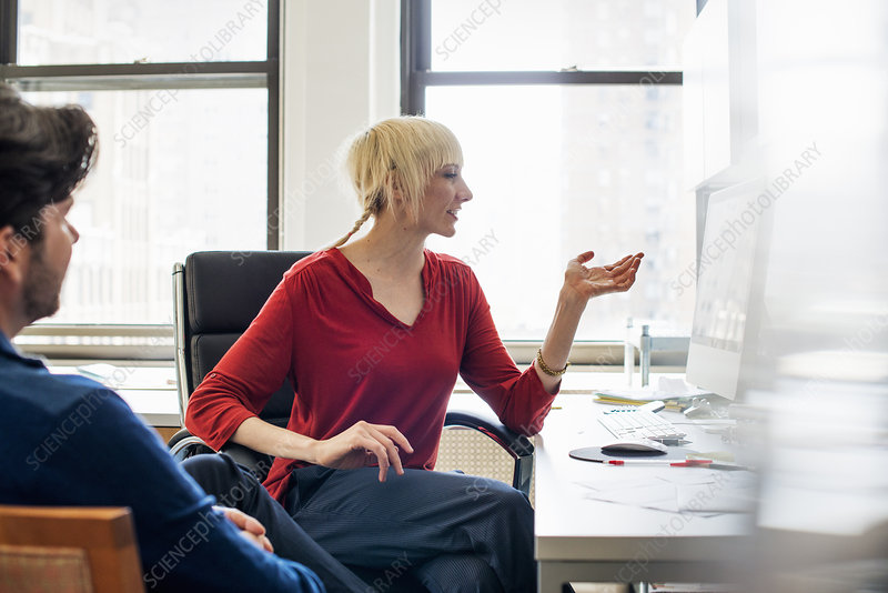 A man and woman in an office talking