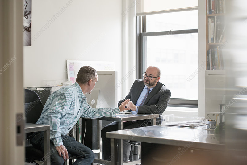 Two men seated talking to each other