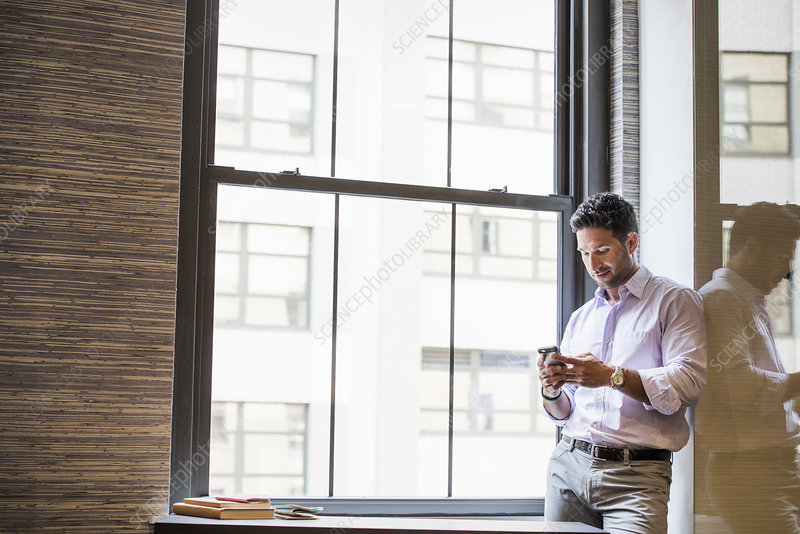 A man in office checking a smart phone