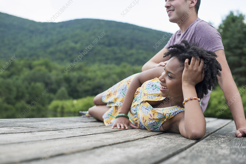A couple relaxing on a jetty by a lake
