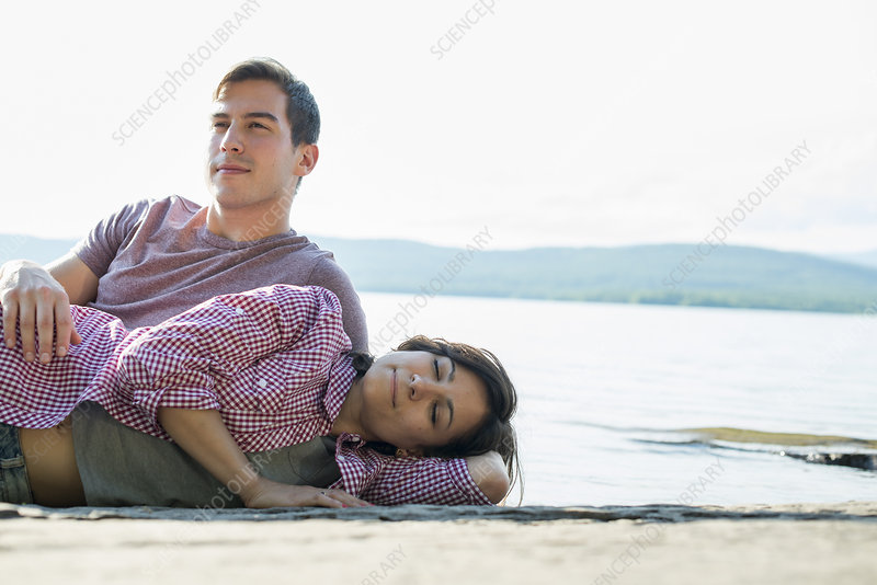 Couple relaxing, lying on a wooden jetty