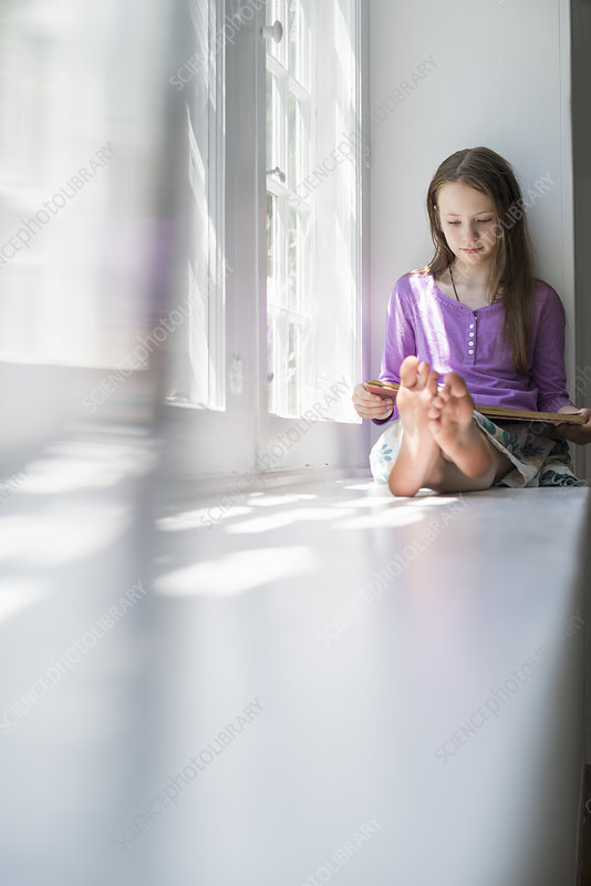 Girl sitting by a window, reading a book