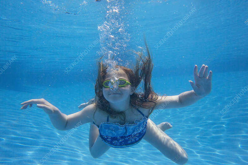A child swimming underwater in a pool