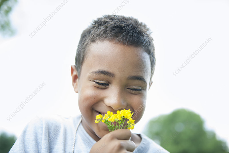 Boy smiling and holding flower