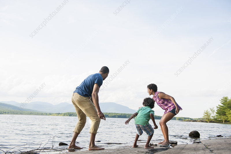 Mother, father and son playing by a lake
