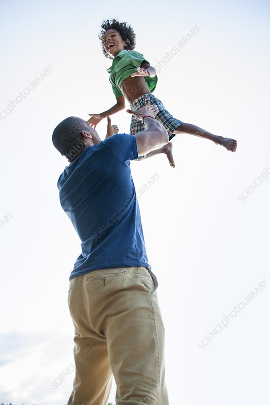 A man lifting a small boy up in the air