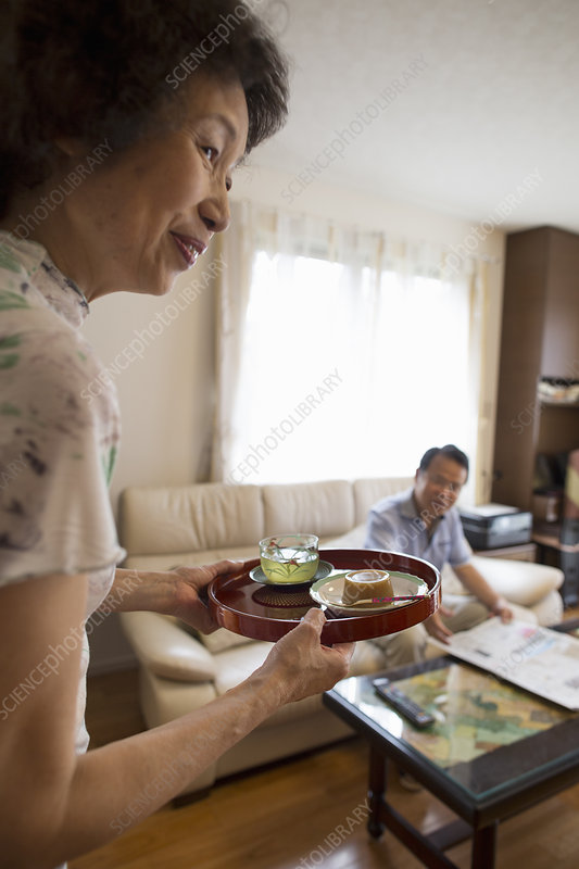 A woman serving tray of food to man