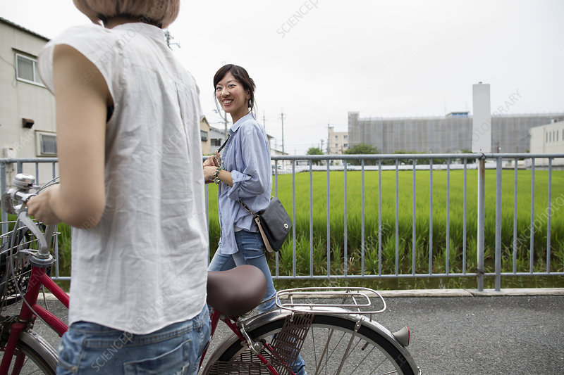 Two women walking pushing a bicycle
