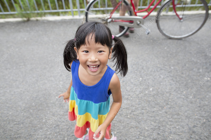 A young girl with pigtails smiling
