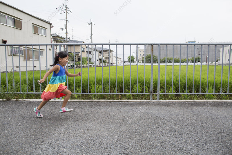 A young girl running along a footpath