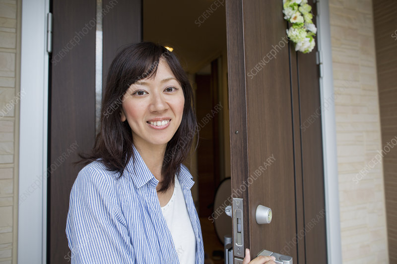A woman standing at her front door
