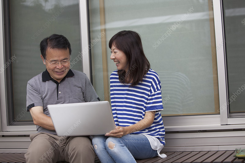 A man and woman Holding laptop computer