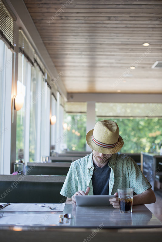 A man in a diner using a digital tablet