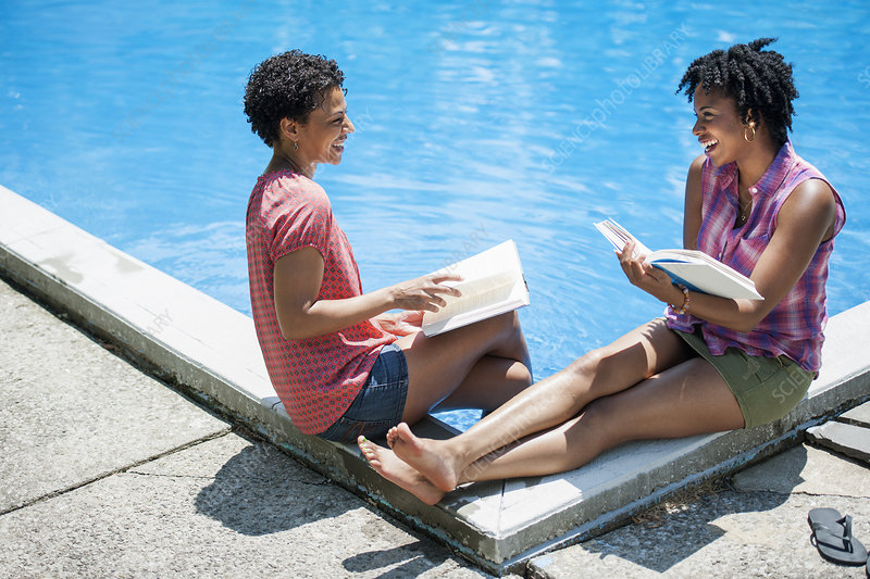 Two women sitting by pool, reading books