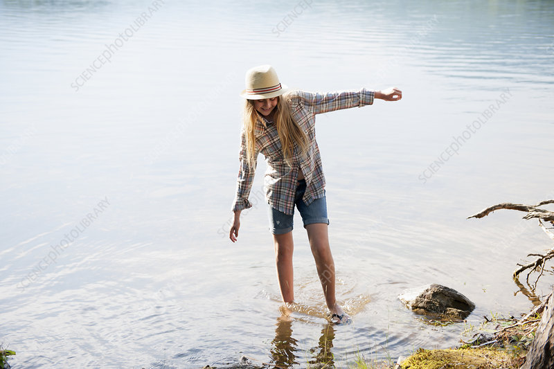 A girl in straw hat paddling in a lake