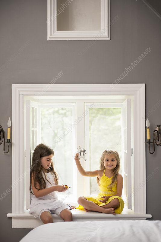 Two girls playing together by a window