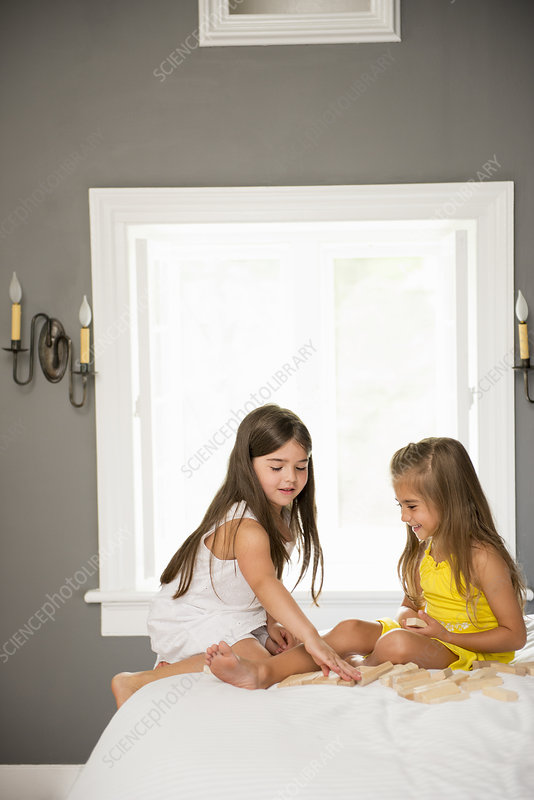 Two girls together playing in a bedroom