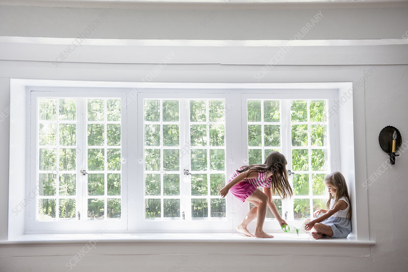 Two girls playing, sitting on a ledge