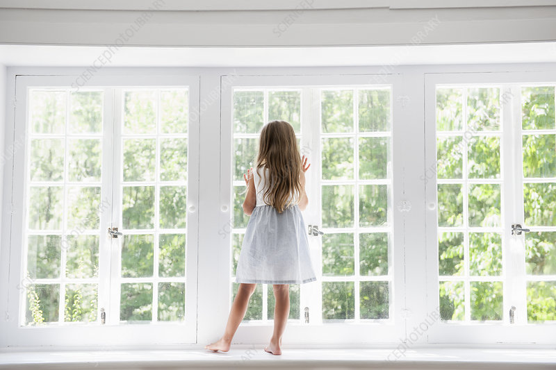A child standing at window looking out