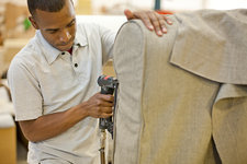 Upholsterer attaching textile to sofa