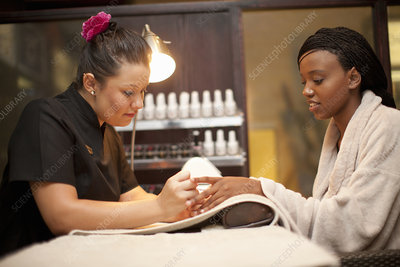 Young woman having nail manicure in spa