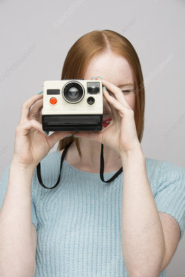 Young woman with polaroid camera