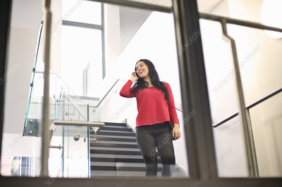 Young woman on staircase using cell phone