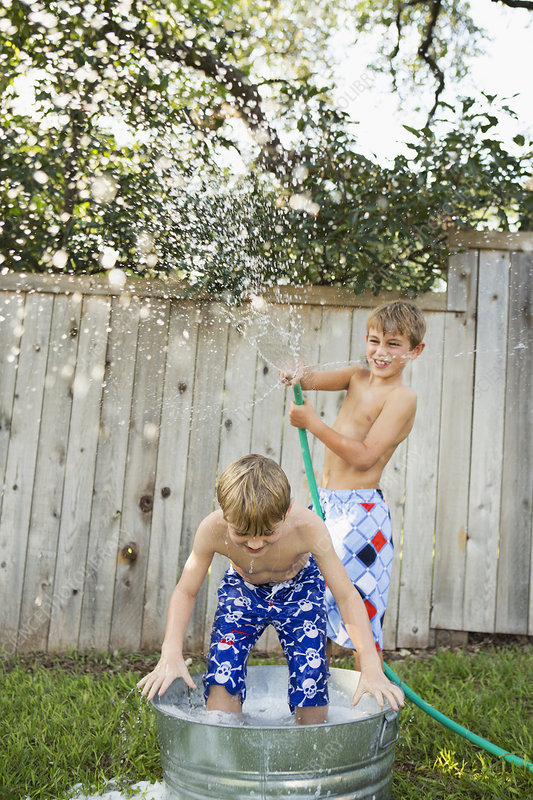 Two brothers playing with water hose