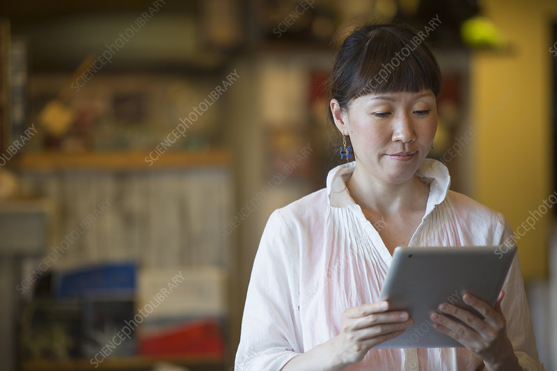 Woman standing in cafe, holding a tablet