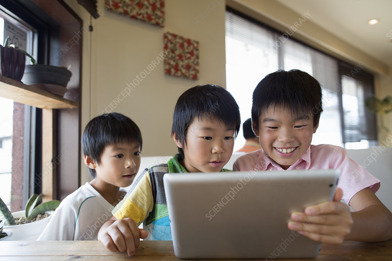 Three boys sitting looking at a tablet