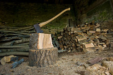 Axe on chopping block, a pile of logs