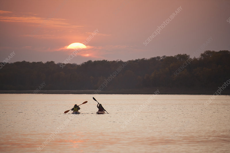 Two kayakers at sunset on a calm lake