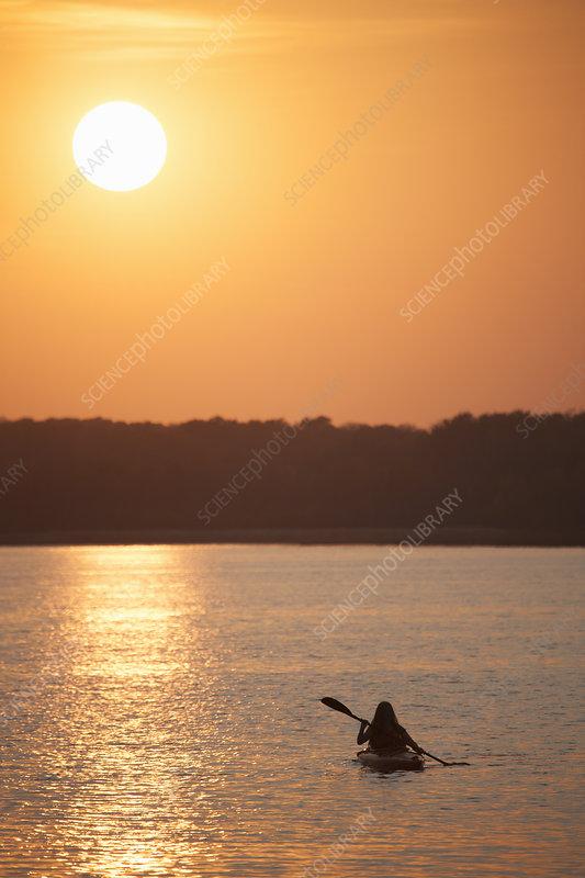 Kayaker at sunset on a calm lake