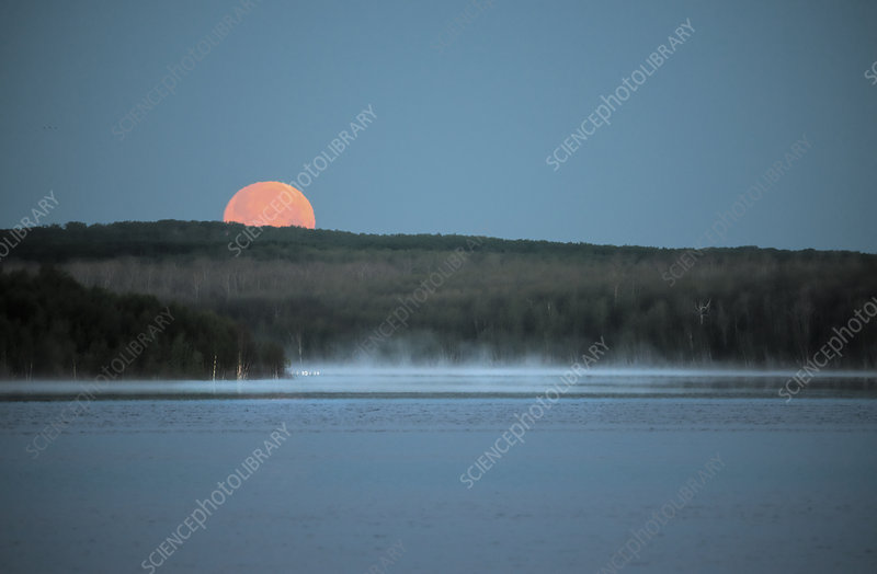 Red moon setting over a lake