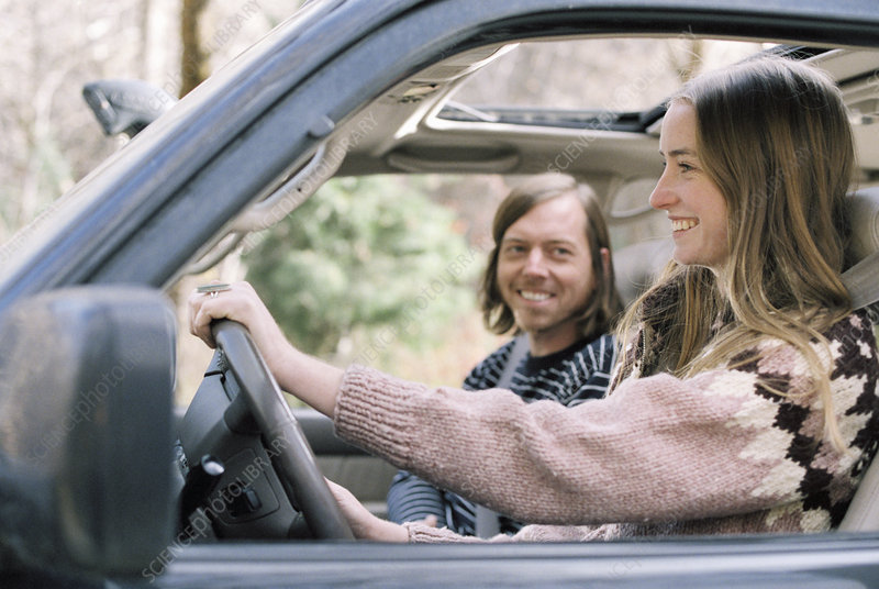 Smiling young couple driving in a car