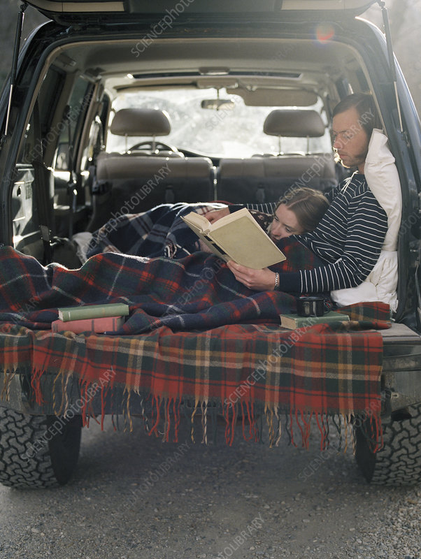Young couple lying reading a book
