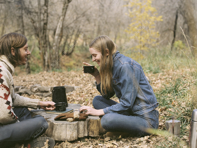 Couple sitting in woods drinking coffee