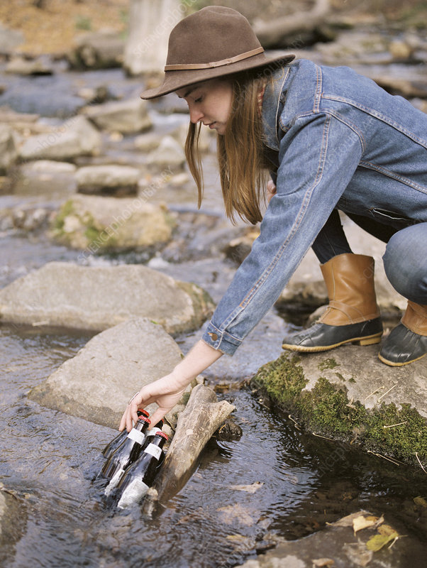 Young woman collecting drinking water