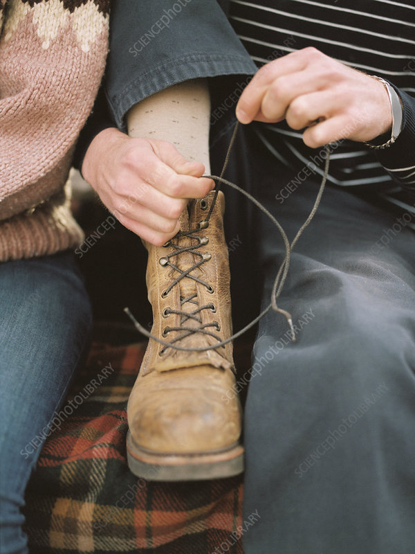 Close up of a man tying his boot laces